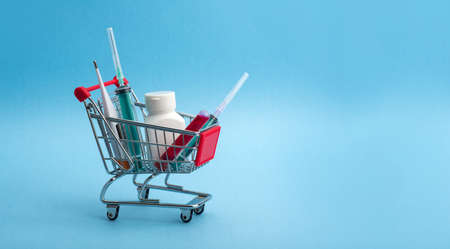 Medicine tablet, Thermometer and syringe or injection with a Test tube containing a blood sample for testing to the presence of virus in shopping cart or trolley.