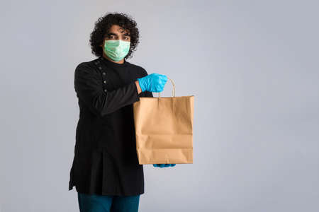 Young man wearing a medical face mask holding and showing paper bag.