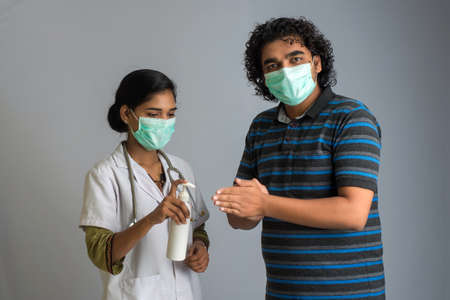 Portrait of young woman doctor and young man using or showing a sanitizing gel from a bottle for hands cleaning.