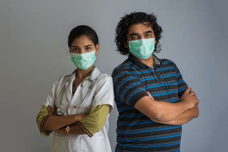 Portrait of young man and woman doctor wearing a protective mask with a stethoscope.