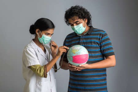 Young man holding earth globe and Female doctor listening to the Earth globe with a stethoscope. 版權商用圖片