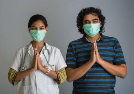 Young man and woman doctor doing Namaste. New greeting to avoid the spread of virus instead of greeting with a hug or handshake. Yoga practice for mental balance. 版權商用圖片