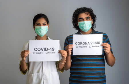 A young woman doctor and man in a medical mask holding board awareness of the epidemic of Coronavirus. 版權商用圖片