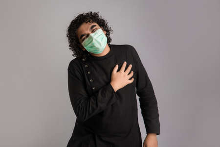 man having a fever wearing a medical mask feeling sick and ill.