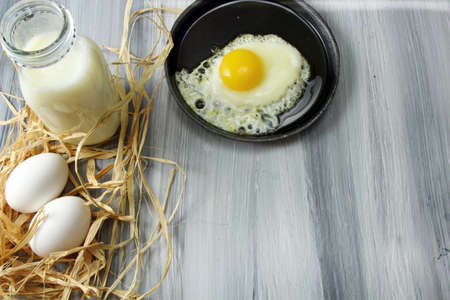 egg cups: Overhead view of white eggs in egg cups surrounded by straw,  milk and a fried egg in an iron skillet on a wooden background with copy space Stock Photo