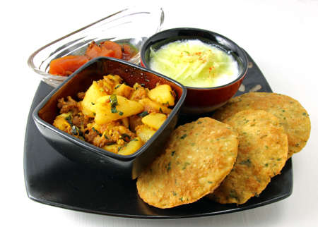 A platter with Spinach Bedmi poori,  potato bhaji ,  apple chutney and yogurt topped with cucumber raita