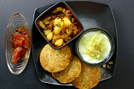sweet and savoury: A platter with Spinach Bedmi poori,  potato bhaji ,  apple chutney and yogurt topped with cucumber raita