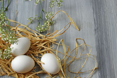 egg cups: Overhead view of white eggs in egg cups surrounded by straw and milk on a wooden background with copy space.