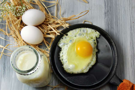 egg cups: Overhead view of white eggs in egg cups surrounded by straw,  milk and a fried egg in an iron skillet on a wooden background with copy space.