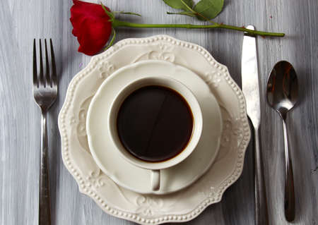 Overhead view of a coffee cup and plate with black coffee and a red Rose.