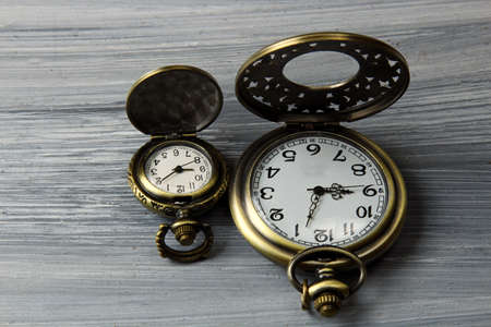 chrome man: Two pocket watches on a grey wooden background.