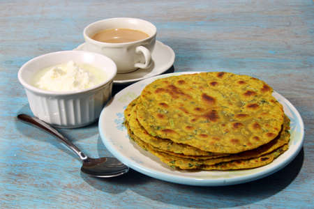 methi: Methi Paratha,an Indian flatbread stuffed with fenugreek leaves and spices served in breakfast or brunch with tea and yogurt.