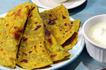methi: Methi Paratha,an Indian flatbread stuffed with fenugreek leaves and spices served in breakfast or brunch .