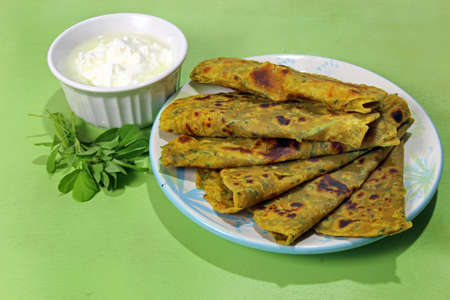 methi: Methi Paratha,an Indian flatbread stuffed with fenugreek leaves and spices served in breakfast or brunch with  yogurt.