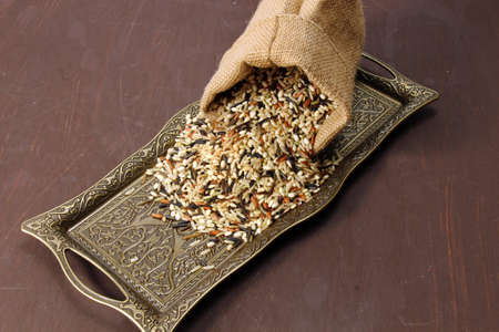 moody background: Wild rice in a burlap bag on a wooden moody background. Stock Photo