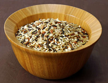 moody background: A wooden bowl on wild rice on a moody background, selective focus. Stock Photo