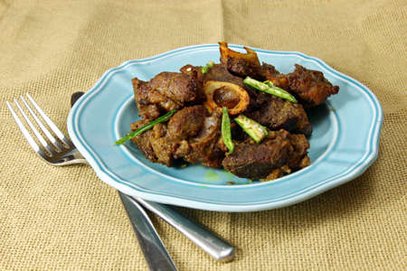 mutton: Mutton fry on a plate on a burlap background.