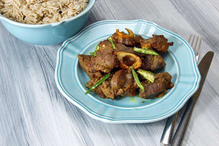 non vegetarian: Mutton fry on a plate with a bowl of aromatic basmati rice on white background.