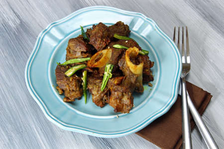 non vegetarian: Mutton fry on a plate on grey background.