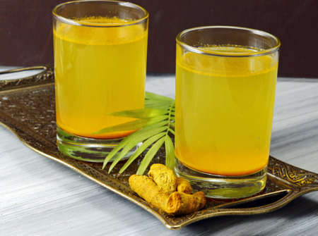 Spicy healthy Haldi or Turmeric and lemon antioxidant drink on a moody background.