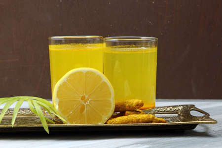 curcumin: Spicy healthy Haldi or Turmeric and lemon antioxidant drink on a moody background.