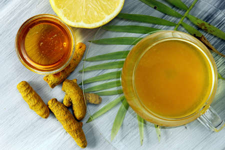 antioxidant: Healthy Haldi or Turmeric with honey and lemon antioxidant tea on a grey background.