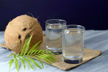 unbroken: Coconut water in two glasses and an unbroken Coconut with green leaves on  a dark background.