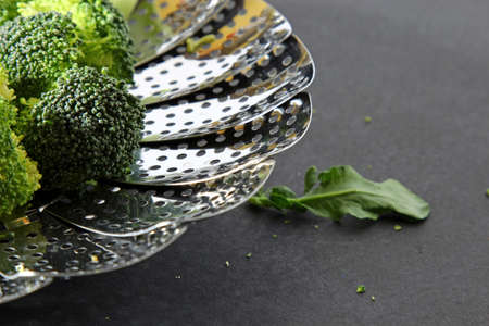 moody background: Fresh Brocolli florets in a steamer strainer with copy space on a moody background, selective focus. Stock Photo