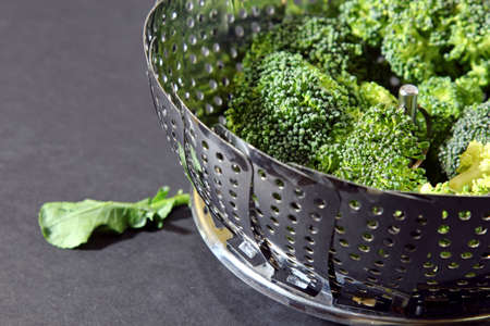 brocolli: Fresh Brocolli florets in a steamer strainer with copy space on a moody background, selective focus. Stock Photo