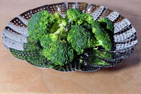 brocolli: Fresh Brocolli florets in a steamer strainer