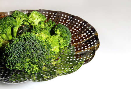 brocolli: Fresh Brocolli florets in a steamer strainer with copy space on a white background, selective focus.