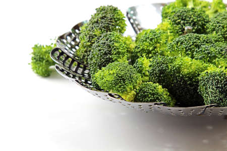 brocolli: Fresh Brocolli florets in a metal strainer for a steamer with copy space, selective focus.