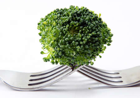 floret: A broccoli floret on two forks on a white background.