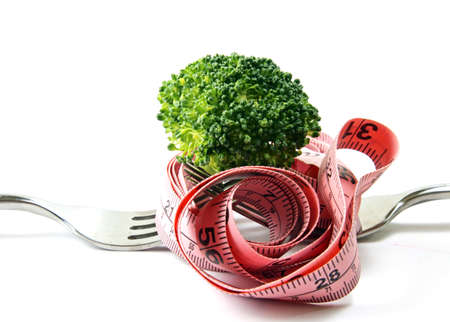 floret: A health concious concept with a broccoli floret on a fork with measuring tape on white background.