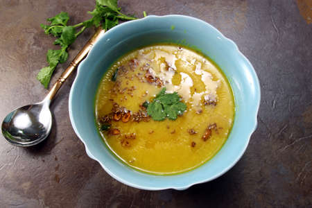 moody background: Overhead view of yellow Lentil soup or Arhar Daal fry with the tadka of cumin seeds, garlic and green chilies on a moody background with copy space