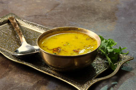 Yellow Lentil soup or Arhar Daal fry with the tadka of cumin seeds, garlic and green chilies in a bowl on a tray with cilantro leaves on the side, selective focus.