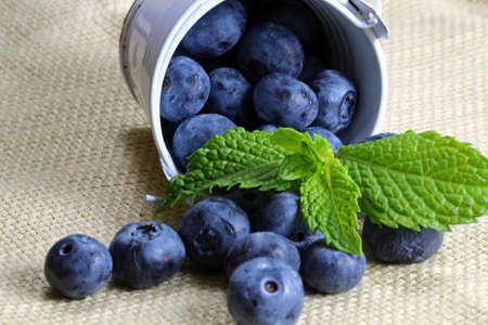 A close up of a container with blueberries and mint leaves with copy space, selective focus