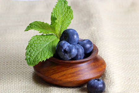 A close up of a container with blueberries and mint leaves