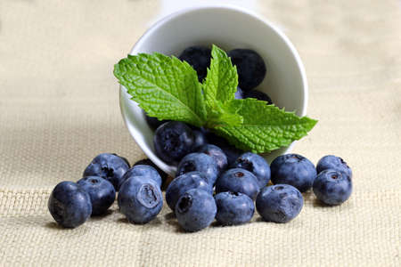 A close up of a container with blueberries and mint leaves, selective focus