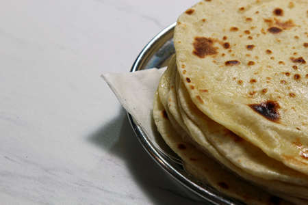 A plate with buttered Kulcha with copy space.