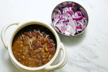 rajma: A bowl of Rajma and chopped Onions on white background with copy space. Stock Photo