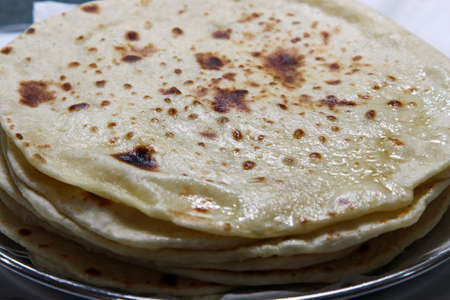 A close up of a stack of buttered Kulcha Stock Photo