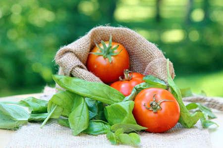 バジルの葉と、コピー領域のフィールドの浅い深さと黄麻布の上の 3 つのチェリー トマト 写真素材