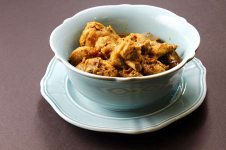 moody background: Spicy and aromatic Chicken curry in a bowl on a moody background