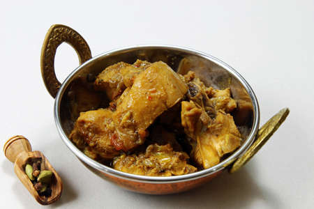 Spicy and aromatic Chicken curry in a kadhai vessel over white background