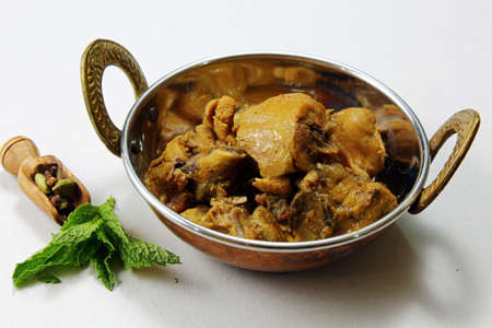 Spicyand aromatic Chicken curry in a kadhai vessel over white background Stock Photo