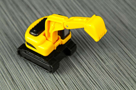 hauler: A yellow toy truck on a grey stone background with copy space, selective focus Stock Photo