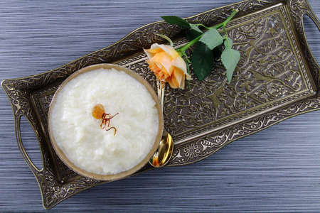 Overhead view of rice kheer or rice pudding in a bowl on a metal tray on grey background with copy space. Stock Photo