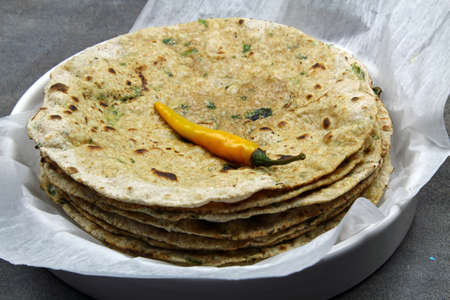 A stack of whole wheat and chopped spinach leaves Chapati or Roti or Tortilla with a hot chili pepper , selective focus. Stock Photo