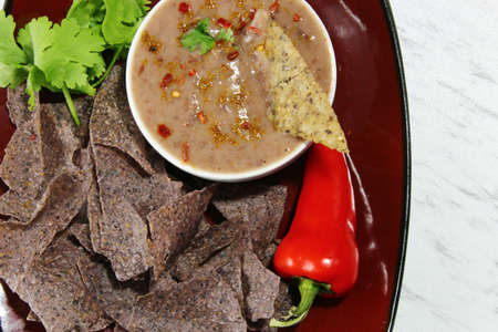 Top view of black bean dip andpurple chips, on a white background with cilantro and red pepper Stock Photo
